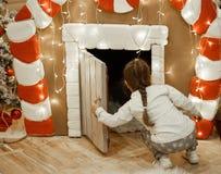Kleines Mädchen schaut in einem Lebkuchenhaus, der Dekor des neuen Jahres, nahe Lichtern und einem Weihnachtsbaum lizenzfreie stockfotografie