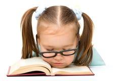 Kleines Mädchen schläft auf einem Buch Stockfotografie