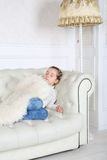 Kleines Mädchen schläft unter weißer Haut auf weißem Sofa Stockfoto