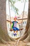 Kleines Mädchen schwingt am Spiel, das zwischen zwei alten riesigen Tannenbäumen gerieben wird Stockbild