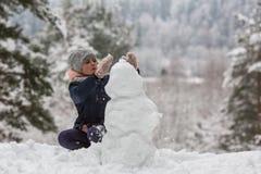 Kleines Mädchen sculpts Schneemann in Winter schneebedecktem Park spiel Stockbild