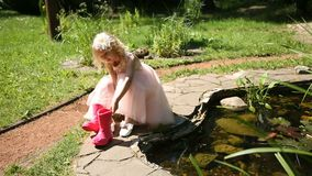 Kleines Mädchen setzt an Gummistiefel stock footage