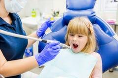 Kleines Mädchen sitts im Zahnarzt ` s Büro stockfotografie