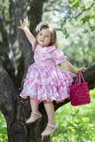 Kleines Mädchen sitzt auf dem Baum Lizenzfreie Stockfotografie