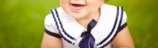 Kleines Mädchen sitzt auf dem grünen Gras im Garten und im Lachen stockfoto