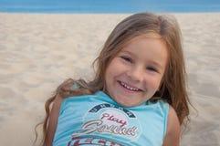 Kleines Mädchen sitzt auf dem Sand auf dem Strand und lacht und glücklich Stockbilder