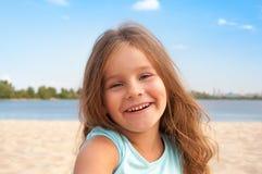 Kleines Mädchen sitzt auf dem Sand auf dem Strand und lacht und glücklich Lizenzfreie Stockbilder