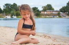 Kleines Mädchen sitzt auf dem Strand Stockfotos