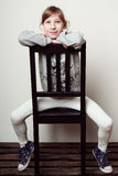 Kleines Mädchen sitzt auf dem Stuhl und lächelt stockbild