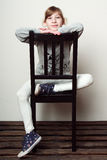 Kleines Mädchen sitzt auf dem Stuhl und lächelt stockbilder