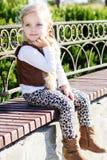 Kleines Mädchen sitzt auf der Bank, Herbstzeit Stockfoto