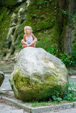 Kleines Mädchen sitzt auf großem Stein Lizenzfreie Stockfotos