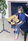 Kleines Mädchen sitzt auf Klavierbank, um Gitarre zu üben stockbilder
