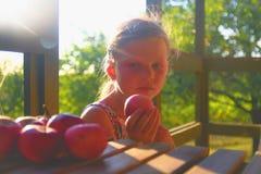 Kleines Mädchen sitzt auf Portal im Sommer Kleines Mädchen isst Äpfel Äpfel auf Tabelle Träumerisches und romantisches Bild lizenzfreie stockfotografie