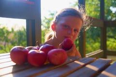 Kleines Mädchen sitzt auf Portal im Sommer Kleines Mädchen isst Äpfel Äpfel auf Tabelle Träumerisches und romantisches Bild stockfotografie