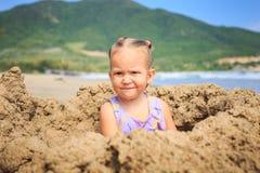 Kleines Mädchen sitzt auf Sand auf Strand gegen Hügel Stockbild