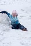 Kleines Mädchen sitzt auf Schnee Stockbilder