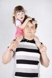 Kleines Mädchen sitzt auf Schultern des Vaters Lizenzfreie Stockfotos