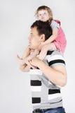 Kleines Mädchen sitzt auf Schultern ihres Vaters und Träume Stockfotografie