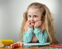 Kleines Mädchen sitzt bei Tisch mit Schal um ihren Hals, nahe Inhalator und Medizin Stockbild