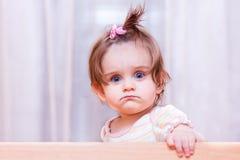 Kleines Mädchen sitzt in der Krippe Stockfotos