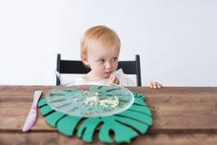 Kleines Mädchen sitzt an einem Tisch Am Mädchen hat ihr geschmackvoller Nachtisch beendet Sie ist umgekippt stockbild