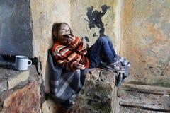 Kleines Mädchen sitzt im Keller und isst Stück Brot stockfoto