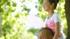Kleines Mädchen sitzt am Mann ` s Hals Sie gehen in den Park familie stock footage