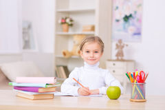Kleines Mädchen sitzt am Schreibtisch und am Handeln Stockbilder