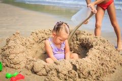 Kleines Mädchen sitzt unter Sand-Haufen-Jungen gießt Wasser auf Strand Stockfotografie