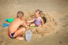Kleines Mädchen sitzt unter Sand-Haufen-Jungen-Hocken durch Spiel auf Strand Stockbild