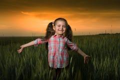 Kleines Mädchen am Sonnenuntergang Stockbilder