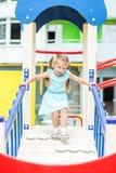 Kleines Mädchen spielt auf dem Spielplatz Das Konzept der Kindheit, Lebensstil, Erziehung, Kindergarten stockfotografie