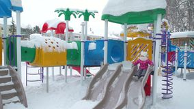 Kleines Mädchen spielt auf einem Schnee bedeckten Spielplatz stock video