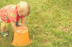 Kleines Mädchen spielt mit einem leeren Eimer Stockfoto