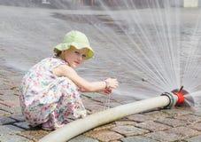 Kleines Mädchen spielt mit einem Spray des Wassers Stockfoto