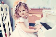 Kleines Mädchen spielt Musik auf dem Klavier Lizenzfreie Stockbilder