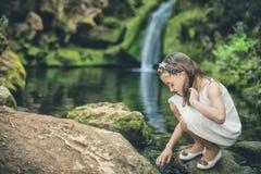 Kleines Mädchen spielt süß mit Wasser neben dem Flussbett Lizenzfreie Stockfotos