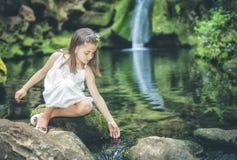 Kleines Mädchen spielt süß mit Wasser neben dem Flussbett Lizenzfreie Stockfotografie