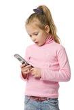 Kleines Mädchen spricht durch Handy Stockbild