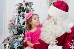 Kleines Mädchen spricht mit Santa Claus Lizenzfreies Stockfoto