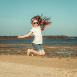 Kleines Mädchen springen auf einen Strand Stockfotografie