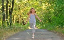 Kleines Mädchen springt über Seil Stockfoto