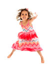 Kleines Mädchen springt in die Luft und feiert seiend aktiv stockfoto