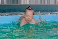 Kleines Mädchen springt in Wasser im Pool Lizenzfreie Stockbilder