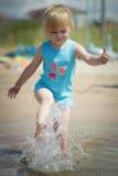 Kleines Mädchen spritzt Wasser im Sommer Lizenzfreie Stockbilder