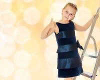 Kleines Mädchen steht auf der Treppe und zeigt Daumen Stockbild