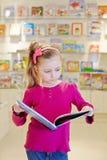 Kleines Mädchen steht Leseoffenes buch Lizenzfreie Stockfotos