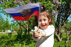 Kleines Mädchen steht mit Flagge von Russland vor Fliederbusch am sonnigen Tag Lizenzfreies Stockbild