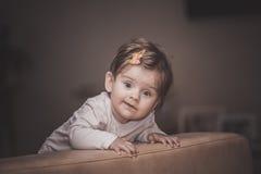 Kleines Mädchen steht nahe dem Sofa zu Hause Stockbild